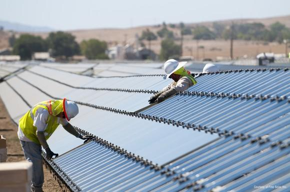 Two workers installing solar panels at large solar project.