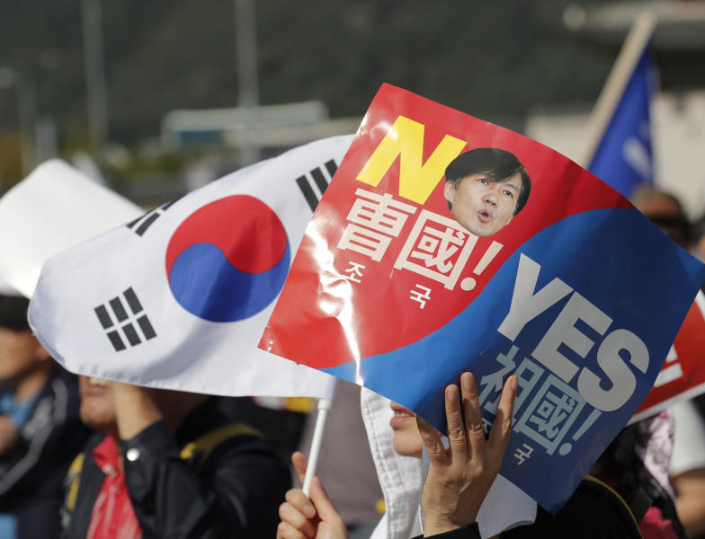 A demonstrator holds a national flag and sign with a picture of South Korea's Justice Minister Cho Kuk during a rally in Seoul, South Korea, Wednesday, Oct. 9, 2019. Thousands of protesters rallied Wednesday in South Korea's capital for the second consecutive week to call for the ouster of President Moon Jae-in's hand-picked justice minister, whose family is at the center of an investigation into allegations of financial crimes and academic favors. (AP Photo/Lee Jin-man)