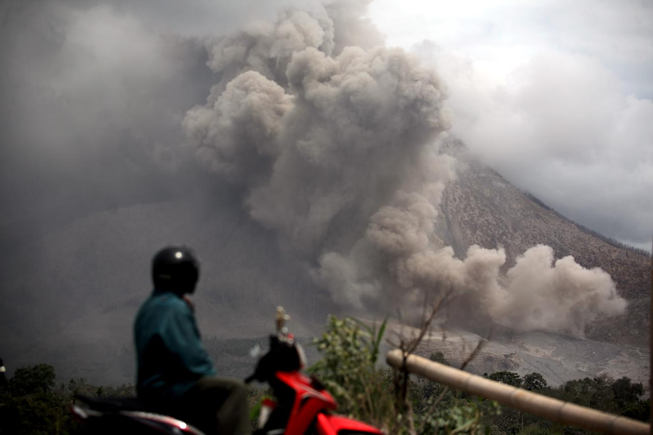 A motorist stops to watch as Mount Sinabung erupts in Tiga Pancur, North Sumatra, Indonesia, Tuesday, Oct. 14, 2014. Mount Sinabung, one of around 130 active volcanoes in Indonesia, has sporadically erupted since 2010 after being dormant for 400 years. (AP Photo/Binsar Bakkara)