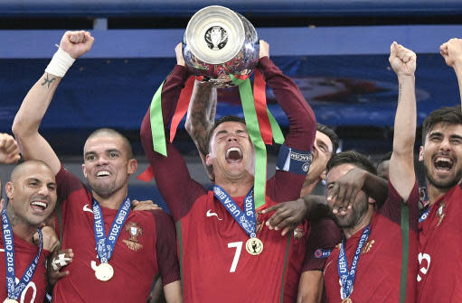 FILE - In this Sunday, July 10, 2016 file photo, Portugal's Cristiano Ronaldo holds the trophy at the end of the Euro 2016 final soccer match between Portugal and France at the Stade de France in Saint-Denis, north of Paris. Cristiano Ronaldo and Lionel Messi put up impressive numbers, in life and on the field, going into a fourth World Cup for each. So much has happened for football's standout stars since the 2014 tournament left both still lacking the game's most coveted prize. (AP Photo/Martin Meissner, File)