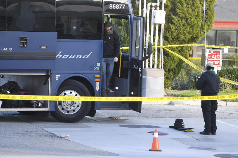 Investigators are seen outside of a Greyhound bus after a passenger was killed on board. Source: AP