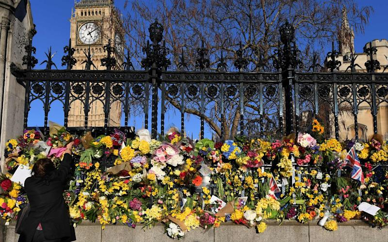 A wellwisher lays flowers outside the Houses of Parliament, following the March 22 attack by Khalid Masood - Credit: AFP