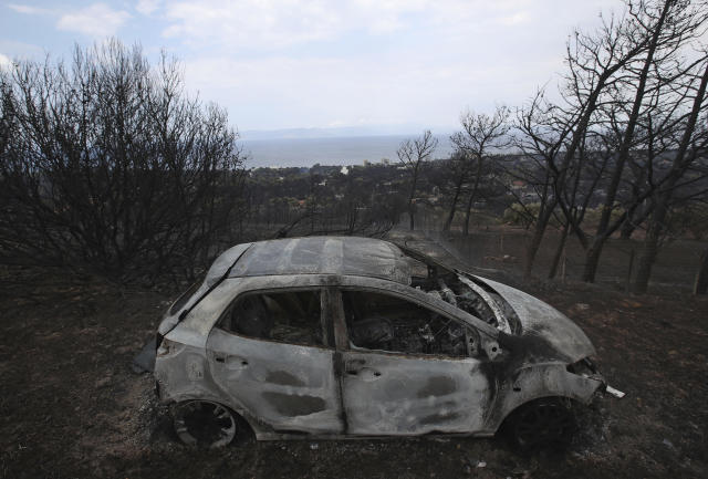 <p>A fire-damaged car is parked on a hill overlooking the village of Neos Voutzas near Athens, Tuesday, July 24, 2018. (Photo: Thanassis Stavrakis/AP) </p>