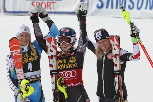 Mikaela Shiffrin, of the United States, center, winner of an alpine ski, Women's World Cup finals slalom, celebrates on the podium with second-placed Sweden's Frida Hansdotter, left, and third-placed Austria's Marlies Schild, in Lenzerheide, Switzerland, Saturday, March 15, 2014. (AP Photo/Armando Trovati)