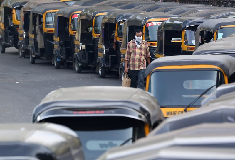 FILE PHOTO: A man wearing a handkerchief as a mask moves past parked autorickshaw during a curfew to limit the spreading of coronavirus disease (COVID-19), in Mumbai