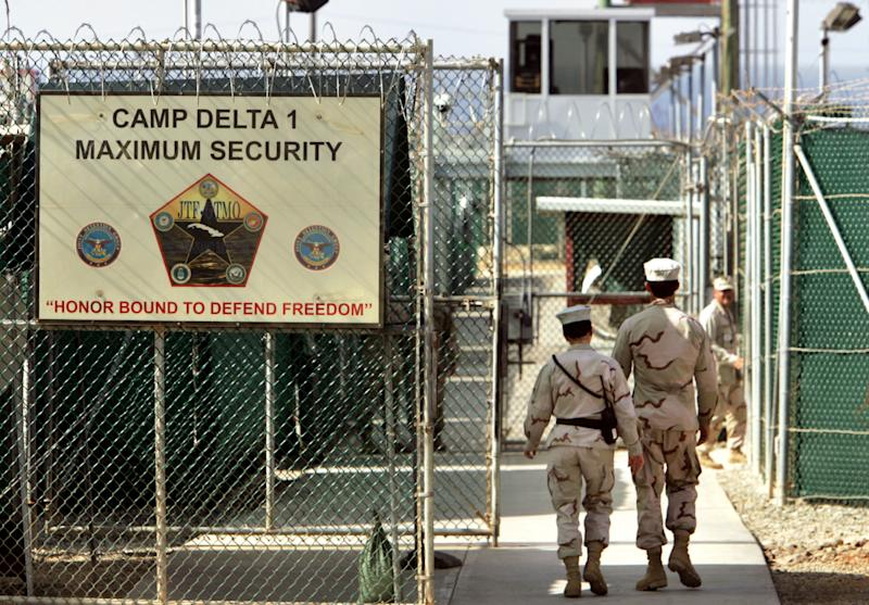 FILE - In this June 27, 2006 file photo, reviewed by a U.S. Department of Defense official, U.S. military guards walk within Camp Delta military-run prison, at the Guantanamo Bay U.S. Naval Base, Cuba. The White House is threatening that President Barack Obama would veto the defense bill unless Congress makes changes. The Office of Management and Budget issued a statement Thursday as the Senate debated the $631 billion bill. Specifically, the White House complained about provisions restricting the administration's ability to transfer detainees from the U.S. Naval facility at Guantanamo Bay, Cuba, to foreign countries. The White House also complained about the prohibition on funds to build a detention facility in the US.  (AP Photo/Brennan Linsley, File)