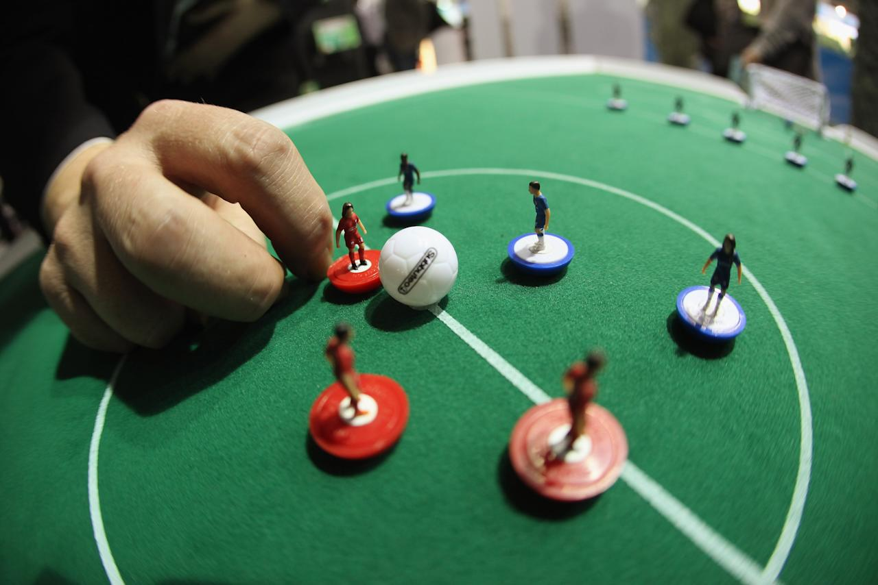 LONDON, ENGLAND - JANUARY 24:  A man plays a game of Subbuteo at the 2012 London Toy Fair, at Olympia Exhibition Centre on January 24, 2012 in London, England. The annual fair, which is organised by the British Toy and Hobby Association, brings together toy manufacturers with retailers from around the world.  (Photo by Oli Scarff/Getty Images)