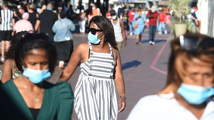 People wearing face masks walk in Cape Town, South Africa on December 27, 2020