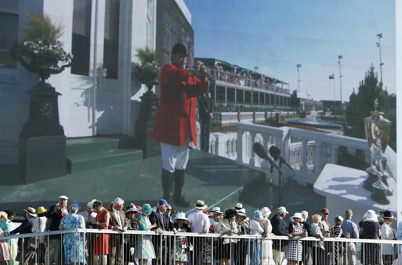 Fans watch the 140th running of the Kentucky Derby horse race at Churchill Downs on a large video screen Saturday, May 3, 2014, in Louisville, Ky. (AP Photo/Matt Slocum)