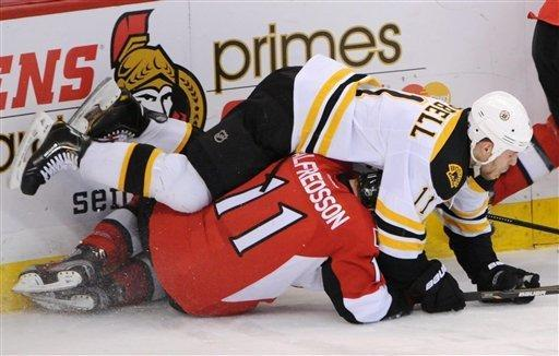 Boston Bruins' Gregory Campbell lands on top of Ottawa Senators' Daniel Alfredsson during the first period of an NHL hockey game in Ottawa, Ontario, on Saturday, Feb. 25, 2011. (AP Photo/The Canadian Press, Sean Kilpatrick)