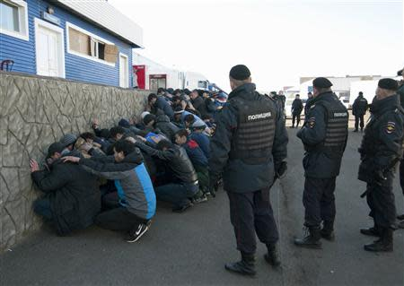 Russian police detain migrant workers during a raid at a vegetable warehouse complex in the Biryulyovo district of Moscow October 14, 2013. REUTERS/Ivan Stolpnikov