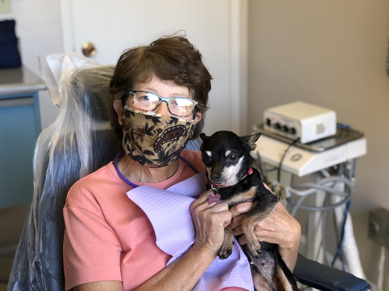 A dental patient in a mask holds Kismet.