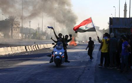 Demonstrators gesture as they ride a motorcycle at a protest during a curfew, three days after the nationwide anti-government protests turned violent, in Baghdad