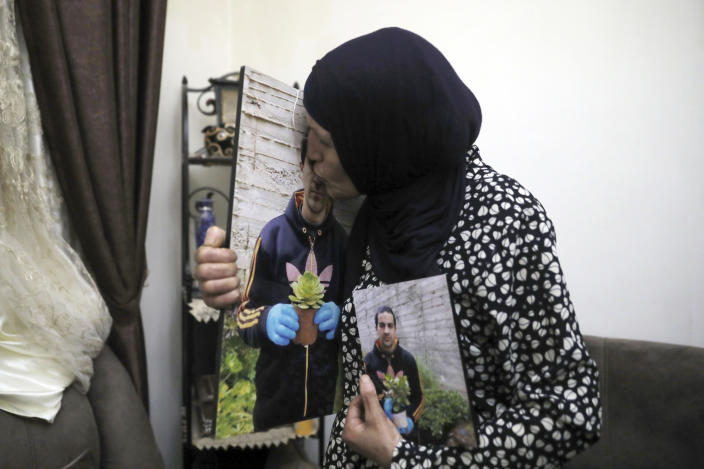 In this Wednesday, June 3, 2020 photo, Rana, mother of Eyad Hallaq, kisses his photo in their home in East Jerusalem's Wadi Joz. Early Saturday, Hallaq, a 32-year-old Palestinian with severe autism, was chased by Israeli border police forces into a nook in Jerusalem's Old City and fatally shot as he cowered next to a garbage bin after apparently being mistaken as an attacker. He was just a few meters from his beloved Elwyn El Quds school. (AP Photo/Mahmoud Illean)