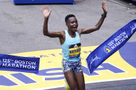 Diana Kipyogei, of Kenya, celebrates at the finish line after winning the women's division of the Boston Marathon in Boston, Monday, Oct. 11, 2021. (AP Photo/Charles Krupa)
