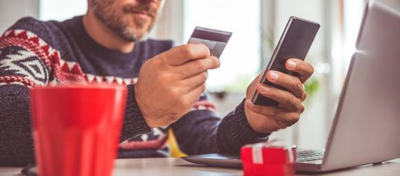 Man shopping on smartphone with credit card in hand.