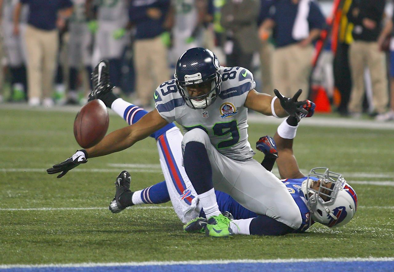TORONTO, ON - DECEMBER 16:  Doug Baldwin #89 of the Seattle Seahawks loses control of the ball after being hit by Justin Rogers #26 of the Buffalo Bills at Rogers Centre on December 16, 2012 in Toronto, Ontario.Seattle won 50-17.  (Photo by Rick Stewart/Getty Images)