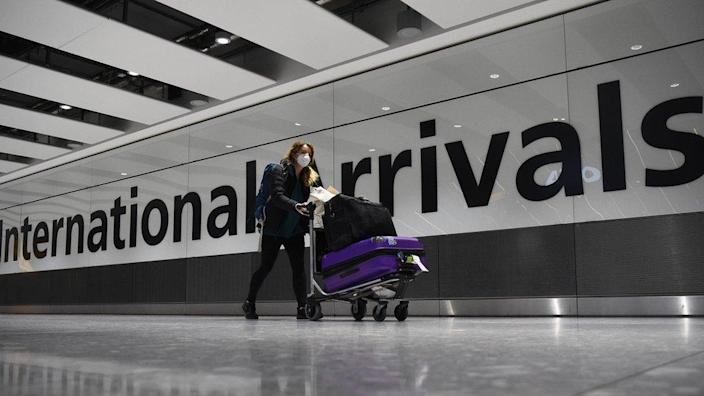 """A passenger pushes luggage through the Arrival Hall of Terminal 5 at London""""s Heathrow Airport"""