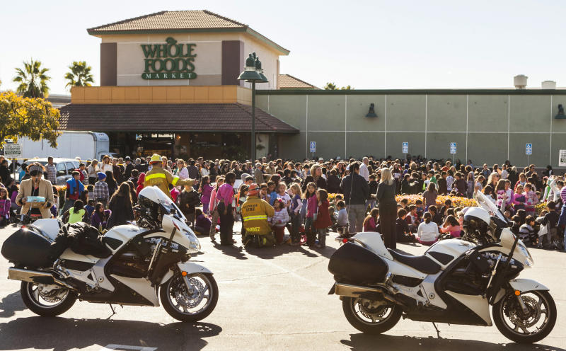 Glendale firemen hold up elementary school children on the parking lot waiting to reunite with their parents after their school was evacuated for a bomb threat in Glendale, Calif., Monday, Jan. 7, 2013. The bomb threat prompted the evacuation of hundreds of children from R.D. White Elementary School on Monday while police searched buildings to make sure the campus was safe. An anonymous caller phoned the school at around 8:30 a.m., and said there was a bomb at the campus, according to police Sgt. Tom Lorenz. (AP Photo/Damian Dovarganes)