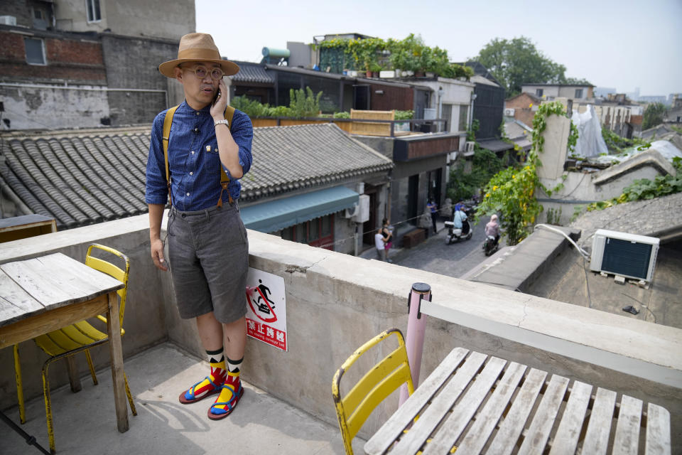 Cafe owner Phil Ma talks on his phone as he stands on the roof of his shop in a neighborhood popular with tourists in central Beijing, Tuesday, Aug. 3, 2021. From the Great Wall to the picturesque Kashmir valley, Asia's tourist destinations are looking to domestic visitors to get them through the COVID-19 pandemic's second year. With international travel heavily restricted, foreign tourists can't enter many countries and locals can't get out. Ma said his cafe has felt the effects of tighter restrictions on travel as China worked to contain outbreaks connected to the Delta variant. (AP Photo/Mark Schiefelbein)