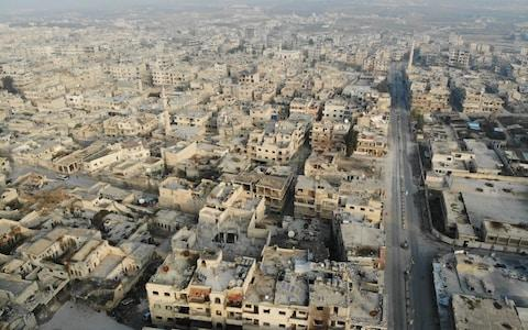A drone picture taken on December 23 shows empty streets and damaged buildings in the town of Maaret al-Numan in the northwestern Idlib province - Credit: AFP