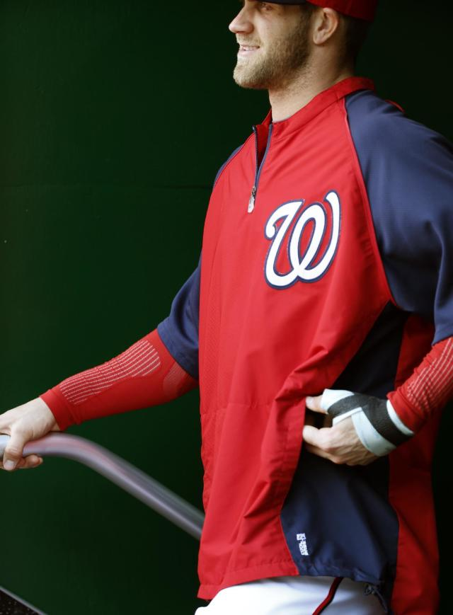 CORRECTS TO LEFT HAND, NOT RIGHT - Washington Nationals left fielder Bryce Harper stands in the dugout with a bandage on his left hand during the fifth inning of a baseball game against the San Diego Padres at Nationals Park Saturday, April 26, 2014, in Washington. Harper injured the hand Friday and is not in the lineup Saturday. (AP Photo/Alex Brandon)