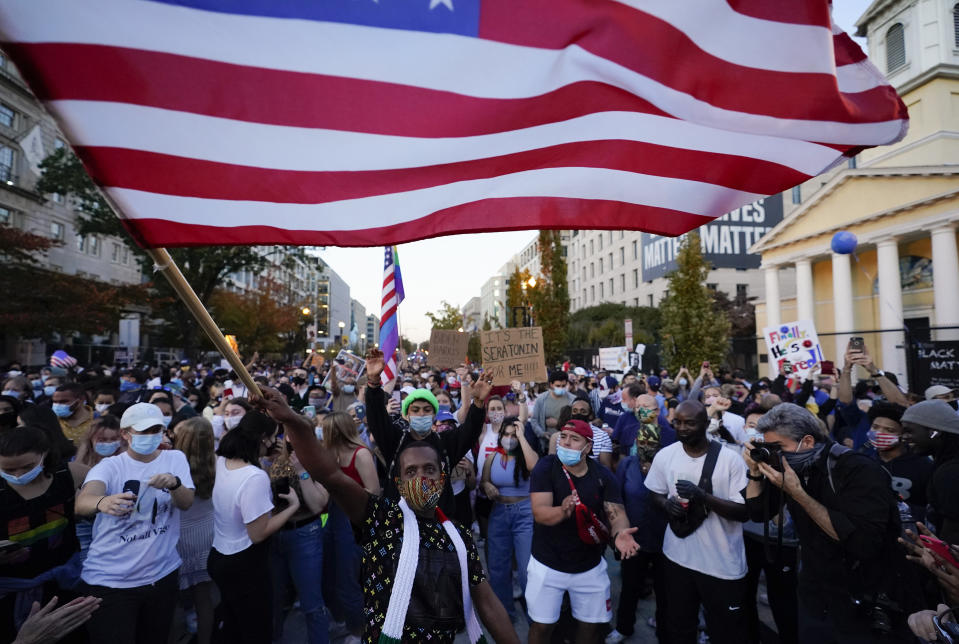 FILE - In this Nov. 7, 2020, file photo, people gather in Black Lives Matter Plaza to celebrate President-elect Joe Biden's win over President Donald Trump to become the 46th president of the United States. (AP Photo/Alex Brandon, File)