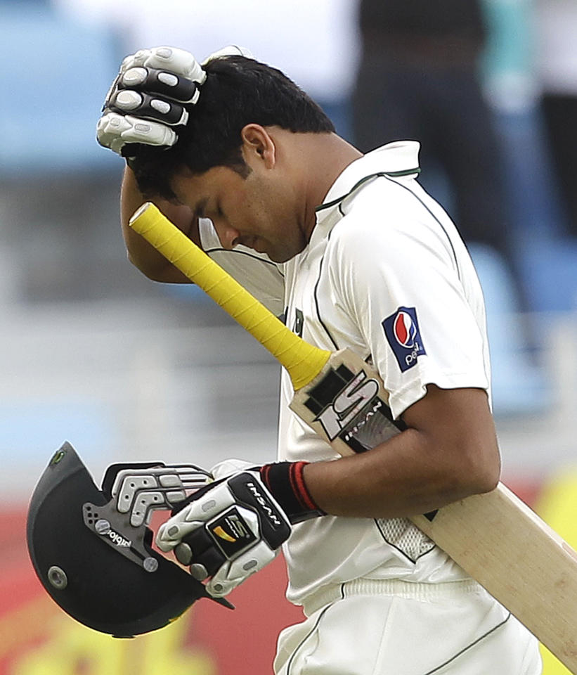 Pakistan's Azhar Ali reacts as walks off the field of play after losing his wicket to England's Graeme Swann during the third day of the third cricket test match of a three match series between England and Pakistan at the Dubai International Cricket Stadium in Dubai, United Arab Emirates, Sunday, Feb. 5, 2012. (AP Photo/Hassan Ammar)