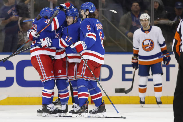 New York Rangers left wing Artemi Panarin (10) celebrates with Rangers right wing Jesper Fast (17) as Rangers defenseman Jacob Trouba (8) joins in after Fast scored against the Islanders during the first period of an NHL hockey game, Monday, Jan. 13, 2020, in New York. (AP Photo/Kathy Willens)