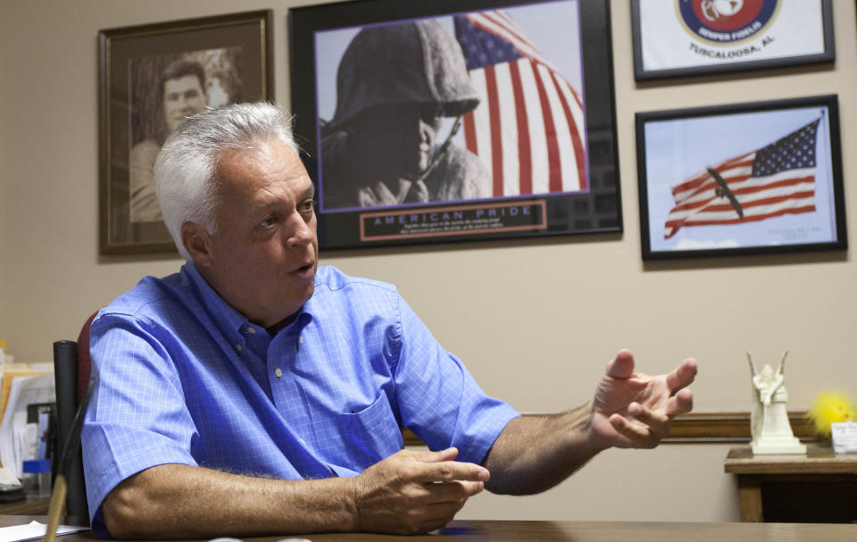 FILE - In this Aug. 9, 2011, file photo, Johnny Spann talks with reporters in his Winfield, Ala., real estate office. His son Mike Spann, a Marine turned CIA officer, felt a duty to go to Afghanistan in the wake of the Sept. 11, 2001, attacks, and in Nov. 2001, he was the first casualty of American service members to be killed in Afghanistan. (AP Photo/Dave Martin, File)