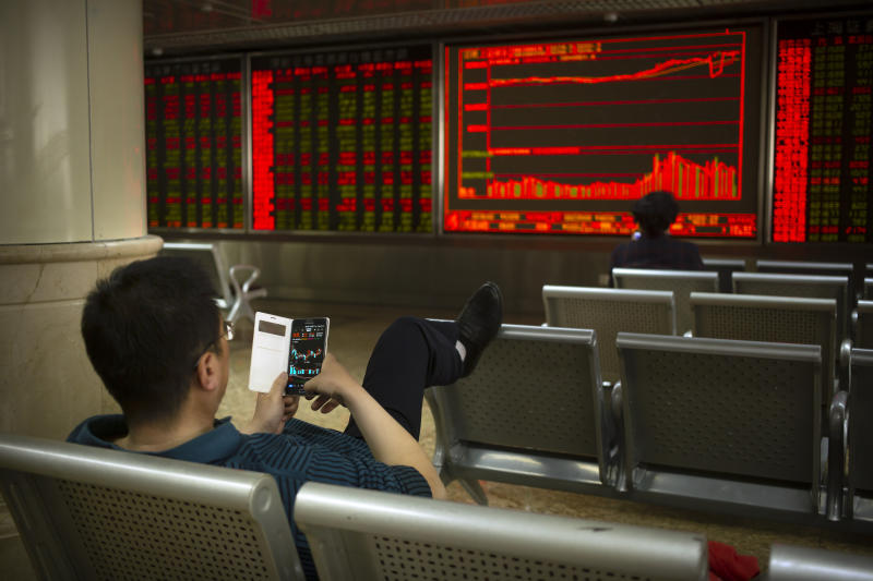 A Chinese investor uses his smartphone as he monitors stock prices at a brokerage house in Beijing, Friday, April 19, 2019. Asian stock indexes rose moderately in quiet holiday trading on Good Friday as some markets were closed. (AP Photo/Mark Schiefelbein)