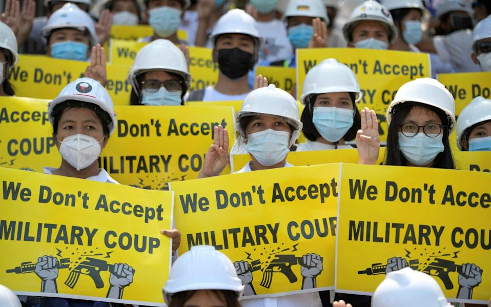 Demonstrators hold placards as they rally against the military coup in Yangon - REUTERS