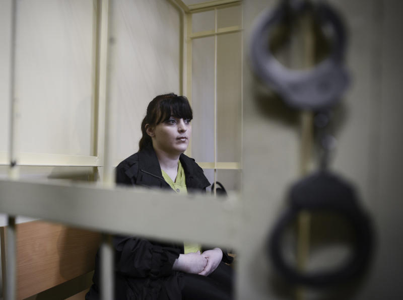 Taisiya Osipova sits behind bars at a courtroom in Russian western city of Smolensk, on Tuesday, Aug. 28, 2012. The Russian opposition activist was sentenced Tuesday to eight years in prison on drug charges, her husband said- twice as long as prosecutors had requested-  in a ruling that drew immediate opposition outrage. Taisiya Osipova has maintained that police planted four grams of heroin in her home in 2010 in revenge for her refusal to testify against her husband, Sergei Fomchenkov, also an activist with The Other Russia opposition movement. (AP Photo/ Mitya Aleshkovskiy)