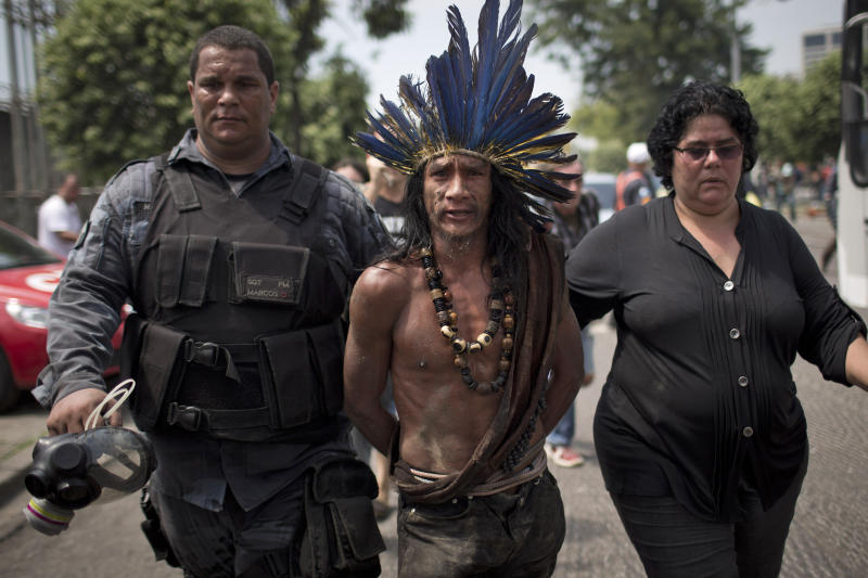 An indigenous man is arrested during clashes outside the old Indian museum, a complex that has been occupied by Indians for years, during an eviction in Rio de Janeiro, Friday, March 22, 2013. Police in riot gear invaded an old Indian museum complex Friday and pulled out a few dozen indigenous people who for months resisted eviction from the building, which will be razed as part of World Cup preparations next to the legendary Maracana football stadium. (AP Photo/Felipe Dana)