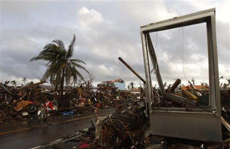 A man rides past a destroyed gasoline pump signboard in the aftermath of super typhoon Haiyan in Tacloban