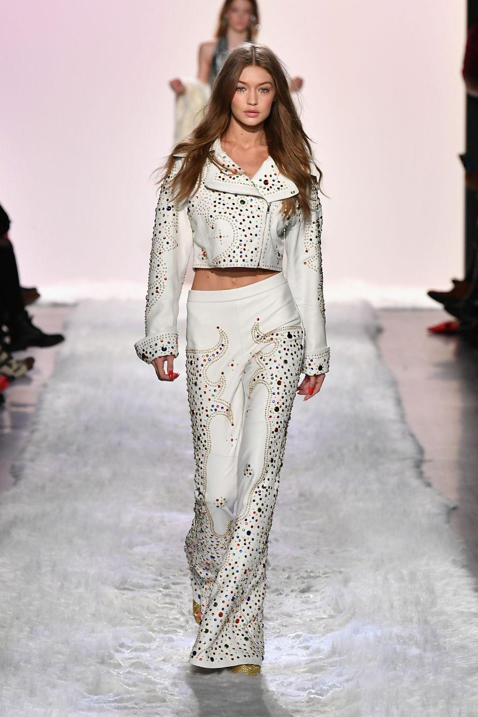 <p>Gigi walked the runway at the Jeremy Scott fashion show in New York City, wearing an Elvis-inspired white leather jacket and trousers.<br><br><br></p>