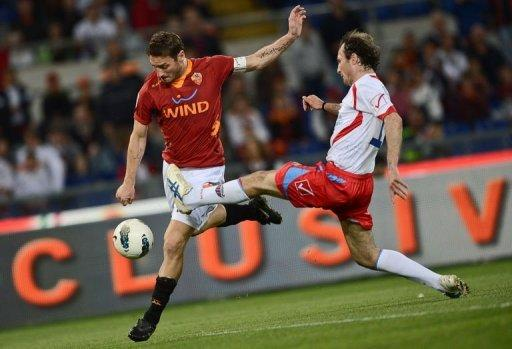 AS Roma's forward Francesco Totti (L) fights for the ball with a Catania player