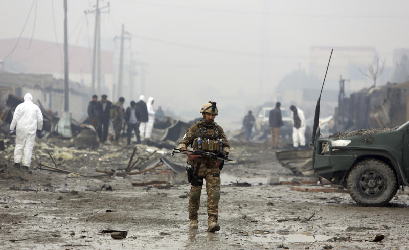 An Afghan security force walks around the site of suicide bomb attack in Kabul, Afghanistan.