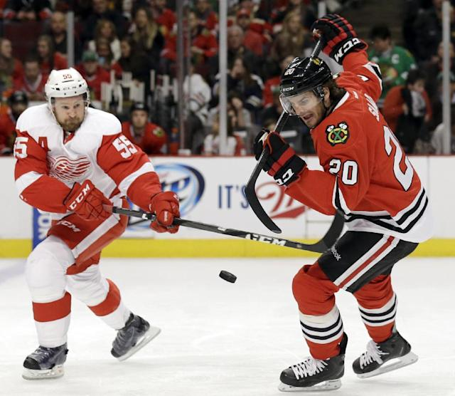 Chicago Blackhawks' Brandon Saad, right, controls the puck against Detroit Red Wings' Niklas Kronwall (55) during the first period of an NHL hockey game in Chicago, Sunday, March 16, 2014. (AP Photo/Nam Y. Huh)