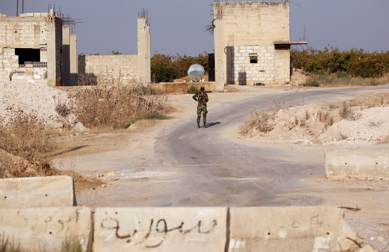 A Syrian army soldier walks in the town of Morek, Hama district