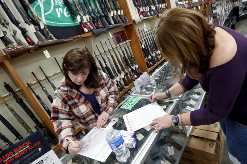 Andrea Schry, right, fills out the buyer part of legal forms to buy a handgun as shop worker Missy Morosky fills out the vendors parts after Dukes Sport Shop reopened, Wednesday, March 25, 2020, in New Castle, Pa. under the new conditions specified for gun stores. The store had closed last week when Pennsylvania Gov. Tom Wolf ordered a shut down of non-essential businesses to slow the spread of the coronavirus. (AP Photo/Keith Srakocic)