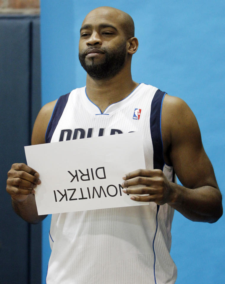 Dallas Mavericks' Vince Carter unknowingly holds up the wrong name card for a photo shoot during NBA basketball media day in Dallas, Tuesday, Dec. 13, 2011. (AP Photo/LM Otero)