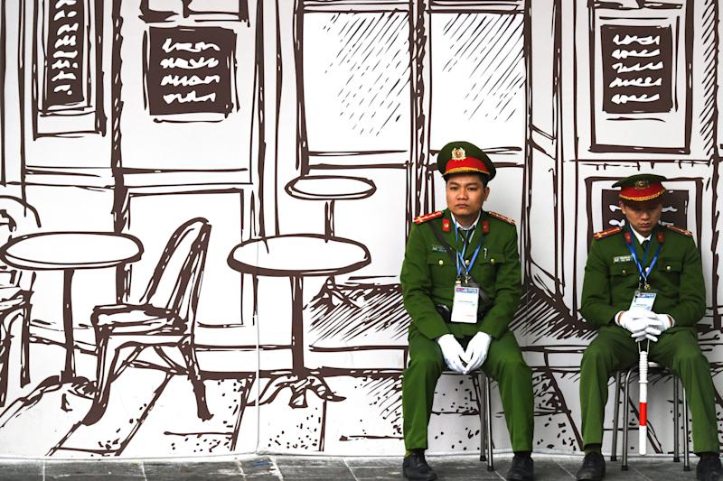 Vietnamese policemen sit on stools near the Sofitel Legend Metropole hotel in Hanoi on February 27, 2019, ahead of the second US-North Korea summit.