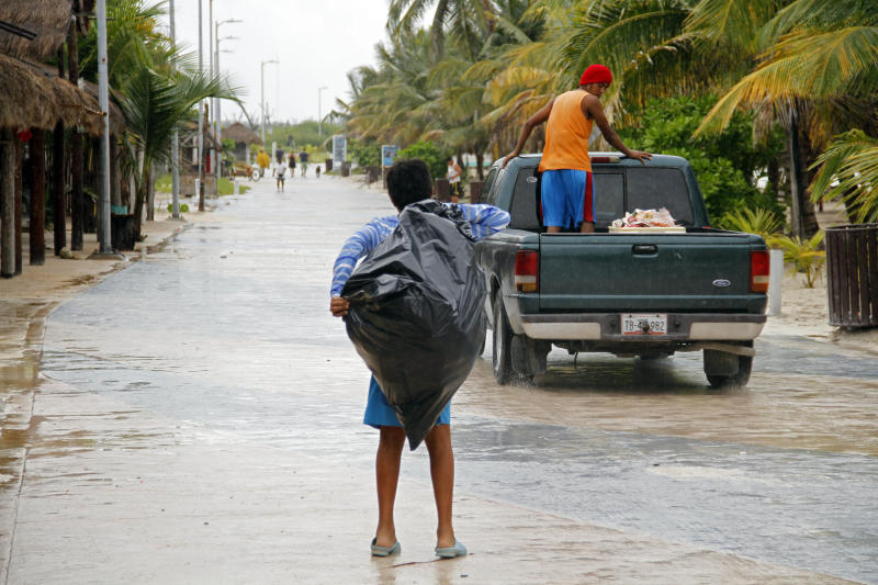Police evacuate residents in Mahahual, Mexico, Tuesday, Aug. 7, 2012 as Tropical Storm Ernesto is expected to slam into the Caribbean coast as a hurricane late Tuesday. The heart of the storm was expected to hit south of Cancun and the Riviera Maya and officials prepared shelters there as a precaution. (AP Photo/Israel Leal)