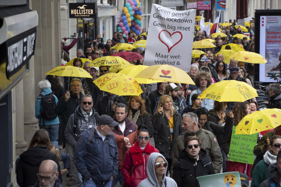 """A banner reads """"No Violence, No Lockdown, No Big Reset, but Freedom and Love"""" during a demonstration against coronavirus related restrictions in Amsterdam, Netherlands, Sunday, May 2, 2021. (AP Photo/Peter Dejong)"""