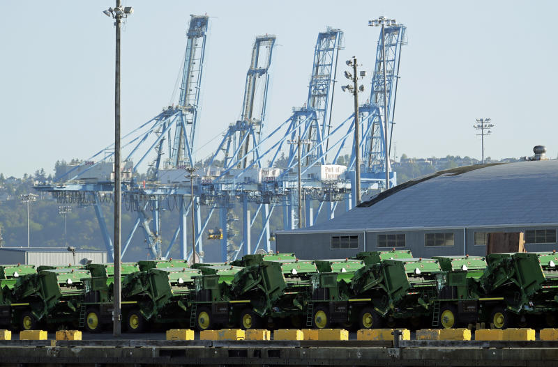 FILE - In this May 10, 2019, file photo John Deere Agricultural machinery made by Deere & Company sits staged for transport near cranes at the Port of Tacoma in Tacoma, Wash. Deere's fiscal second-quarter earnings were a mixed bag and the agricultural equipment maker lowered its full-year outlook as the trade war between the U.S. and China intensifies and conditions in the agricultural sector soften. (AP Photo/Ted S. Warren, File)