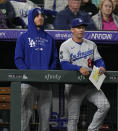 Injured Los Angeles Dodgers center fielder Cody Bellinger, left, looks on with first base coach Clayton McCullough in the ninth inning of a baseball game against the Colorado Rockies Tuesday, Sept. 21, 2021, in Denver. (AP Photo/David Zalubowski)