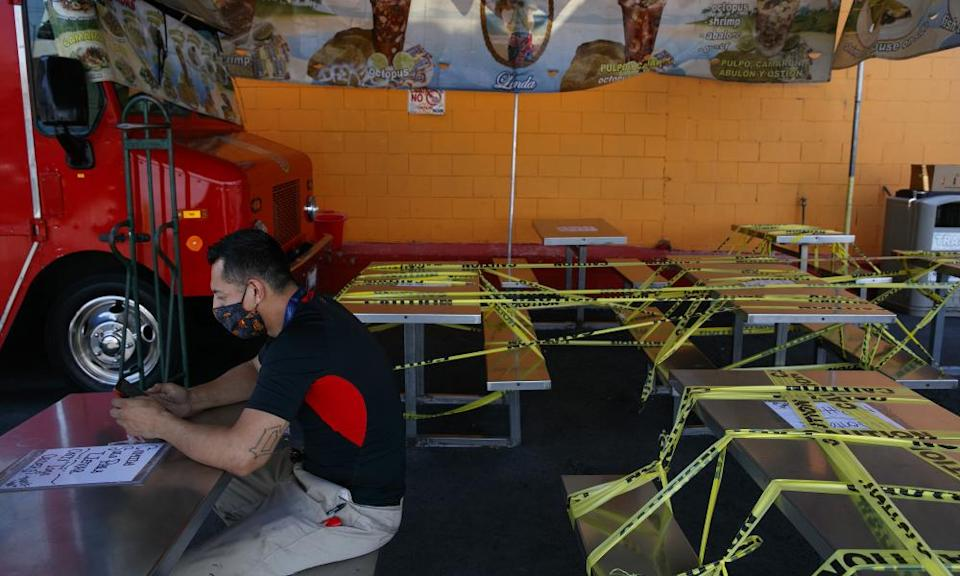 """<span class=""""element-image__caption"""">A man waits for his order at a food truck while dining tables are sealed off with caution tape in Los Angeles, California, on 1 July.</span> <span class=""""element-image__credit"""">Photograph: Jae C Hong/AP</span>"""