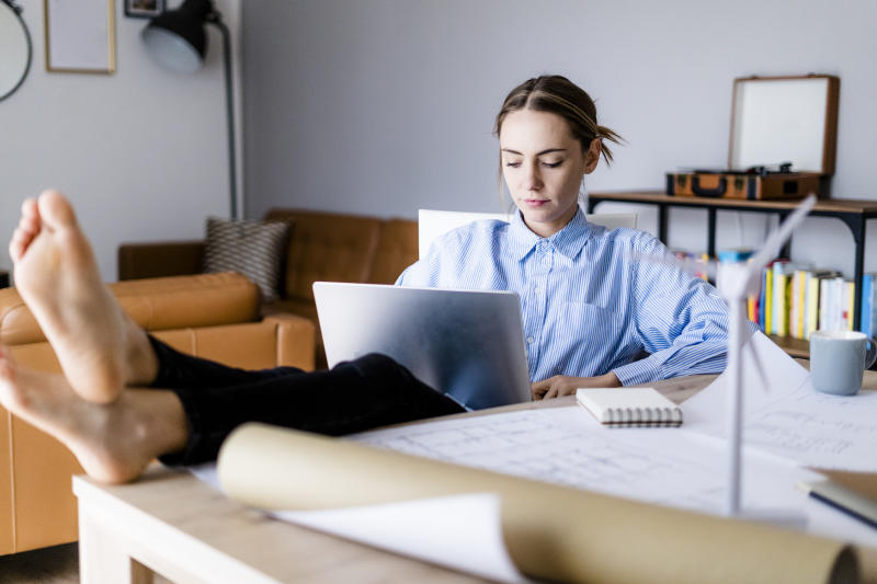 Woman in office working on laptop with feet on table