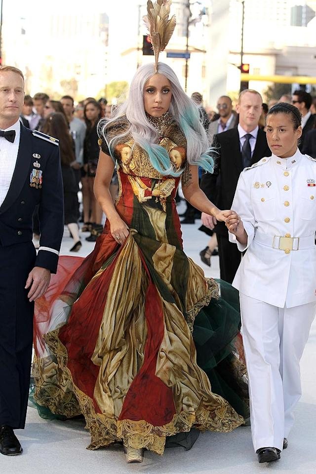 """Lady Gaga looked rather conservative (for her) while making her grand entrance at the 2010 MTV Video Music Awards in a dramatic Renaissance-inspired gown from Alexander McQueen's last collection. The pop star topped off her blue, lilac, and gray locks with a gold feather headpiece. Chris Polk/<a href=""""http://www.gettyimages.com/"""" target=""""new"""">GettyImages.com</a> - September 12, 2010"""